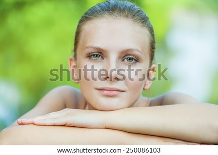 Beautiful young woman with naked shoulders leans against wooden handrail in city park. - stock photo