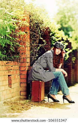 Beautiful young woman with old suitcase walking down the street. - stock photo