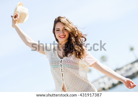 Beautiful young woman with open arms smiling in the beach. - stock photo