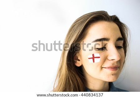 Beautiful young woman with painted english flag on cheek face closeup - stock photo