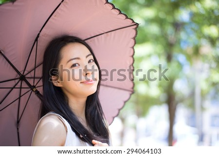 beautiful young woman with parasol - stock photo