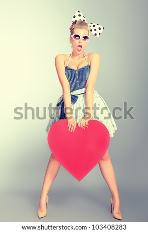 Beautiful young woman with pin-up make-up and hairstyle posing in studio with red hearts. - stock photo