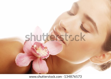 Beautiful young woman with pink orchid over white  background - stock photo