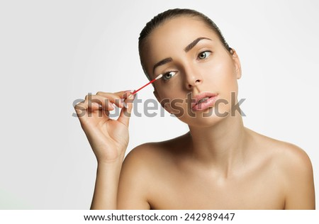 Beautiful young woman  with pure healthy skin and removes makeup from the face with a cotton swab on a gray background - stock photo