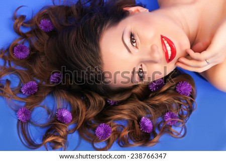 Beautiful young woman with purple flowers on her long hair   - stock photo