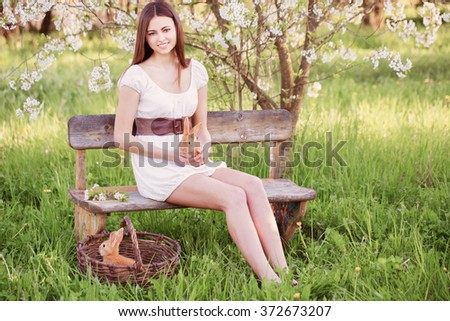 beautiful young woman with rabbits in garden - stock photo