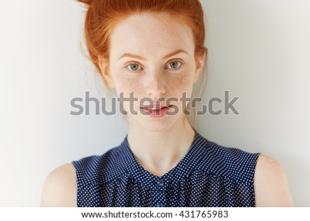 Beautiful young woman with red hair and green eyes in spotted dress, looking and smiling at the camera. Close up portrait of pretty girl with perfect clean freckled skin. People and lifestyle concept - stock photo