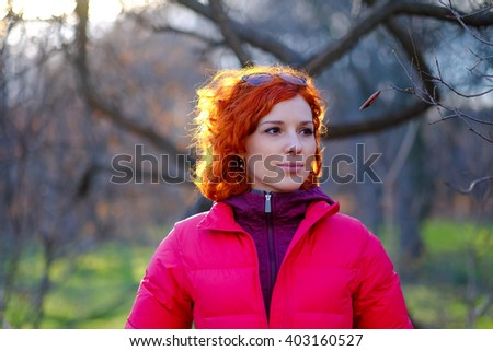 Beautiful young woman with red hair flying in the wind in park in autumn. Girl portrait in fall, warm light sunset. Cold weather, cozy evening outdoors. Walking in the forest on nature. - stock photo