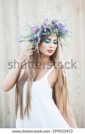 Beautiful young woman with red hair in wreath - stock photo
