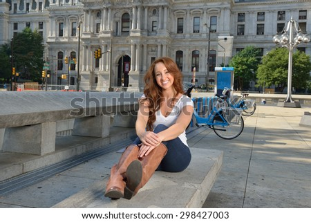 Beautiful young woman with red hair stands in white shirt and blue jeans in city - sitting on stone bench - stock photo