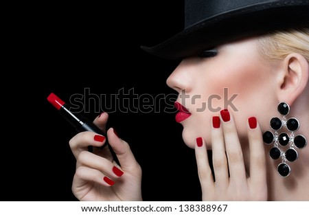 Beautiful young woman with red lips and manicure on black background - stock photo