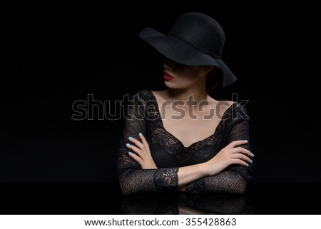 Beautiful young woman with red llips in black hat. Over dark background. Copy space. - stock photo