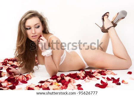 Beautiful young woman with roses petals. - stock photo