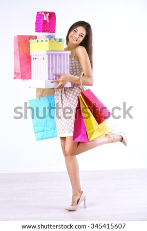 Beautiful young woman with shopping bags and boxes isolated on white - stock photo