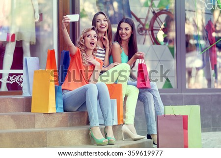 Beautiful young woman with shopping bags sitting on steps - stock photo