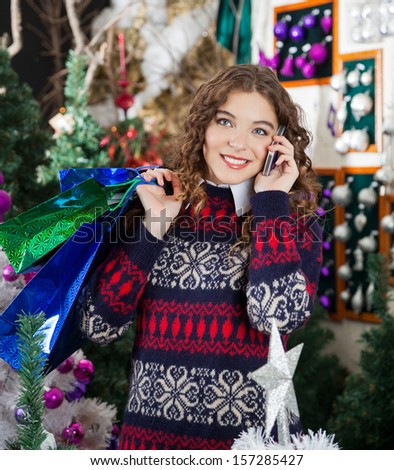 Beautiful young woman with shopping bags using cellphone in Christmas store - stock photo