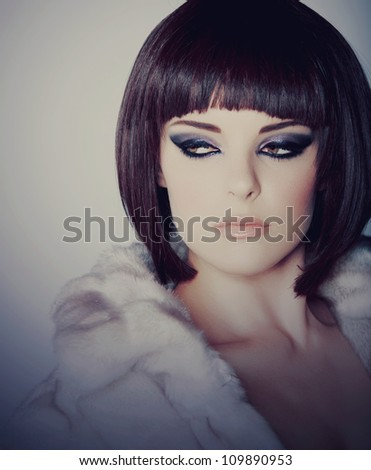 beautiful young woman with short brown hair in white fur coat wearing smoky purple eyeshadow and dramatic eyeliner. - stock photo