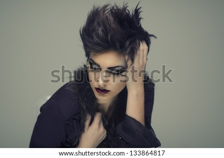 Beautiful young woman with short hair style wearing vintage coat.  Eyes closed looking down with detailed makeup and cosmetic styling. - stock photo