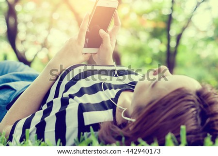 Beautiful young woman with sleeping listen to music in the park,woman mobile phones on nature background, vintage tone  - stock photo