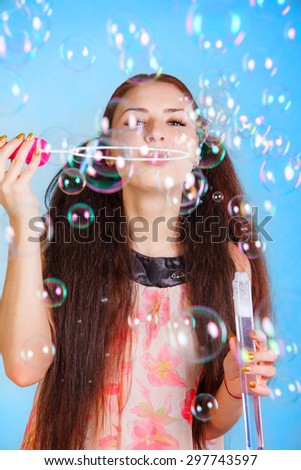 Beautiful young woman with soap bubbles over cyan background - stock photo