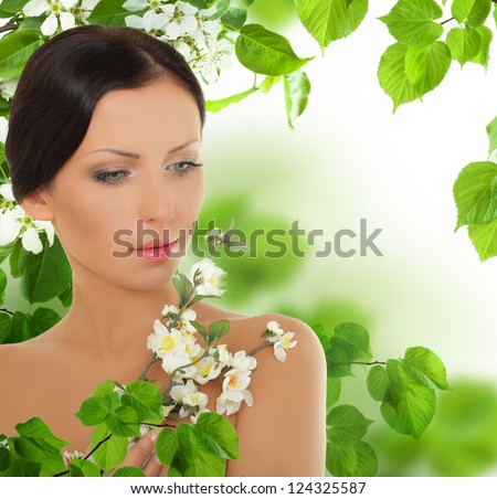 Beautiful young woman with spring blossom - stock photo