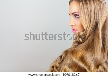 Beautiful young woman with straight long hair on grey background - stock photo