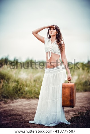 Beautiful young woman with suitcase in hands stands on a rural road - stock photo