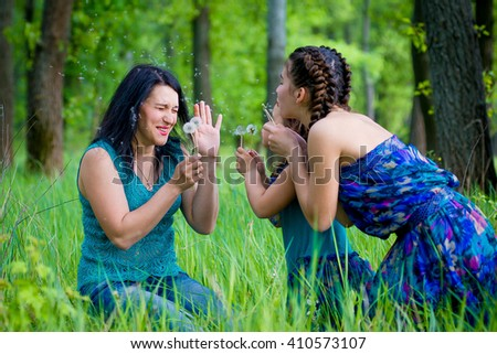 Beautiful Young Woman with Two Children in the park. happy family outdoors. woman and two children having fun.Summer. Mother and daughter in the park. Happy parent and Kids - stock photo