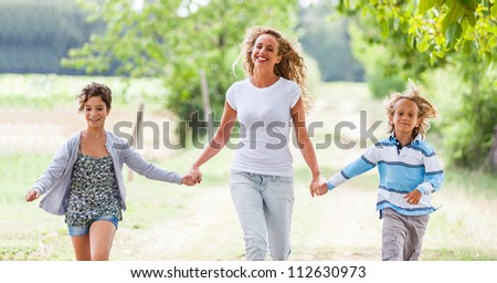 Beautiful Young Woman with Two Children Outside - stock photo
