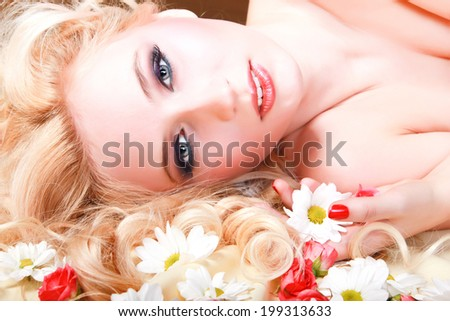 Beautiful young woman with white and pink flowers on her long hair - stock photo