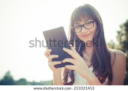 beautiful young woman with white dress using tablet in the city - stock photo