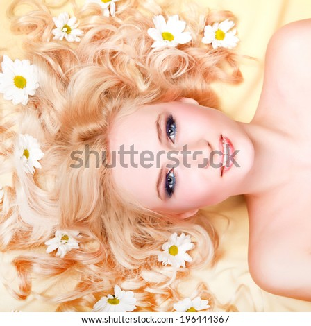 Beautiful young woman with white flowers on her long hair   - stock photo