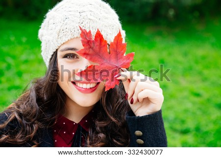 Beautiful young woman with woolen cap covering face with a red leaf while smiling against a green background. Fresh skin and healthy smile. - stock photo