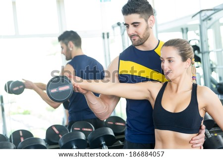 Beautiful young woman working out at the gym with the help of her personal trainer - stock photo