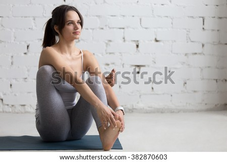 Beautiful young woman working out in loft interior, doing Seated Hip Stretch, hip opener Eka Pada Agni Stambhasana, warming up on blue mat during practice, full length, copy space - stock photo