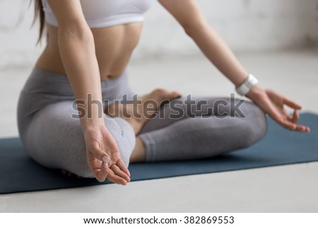 Beautiful young woman working out in loft interior, doing yoga exercise on blue mat, Sitting in Ardha Padmasana, Half Lotus Posture, meditating, breathing, close-up - stock photo