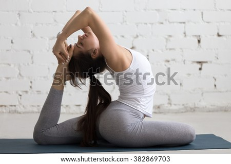 Beautiful young woman working out indoors, doing yoga exercise on blue mat, stretching with closed eyes, Eka Pada Rajakapotasana Pose, One-Legged King Pigeon Posture, full length, side view - stock photo