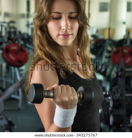 Beautiful young woman working out with weights for her biceps. Attractive slim girl with dumbbells in a gym - stock photo