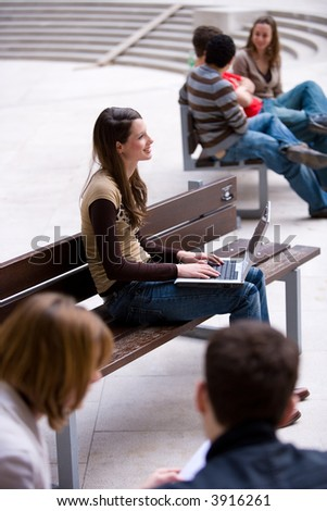 beautiful young woman working with her notebook is sitting outside - stock photo