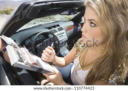 Beautiful young woman writing on traffic ticket - stock photo