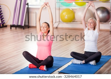 Beautiful young women are doing exercises in fitness center. They are sitting in lotus position and stretching arms up. The girls are smiling. Their eyes are closed with pleasure - stock photo