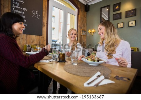 Beautiful young women having food in restaurant - stock photo