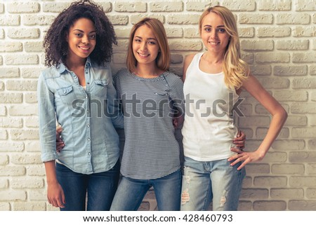 Beautiful young women of different nationalities are looking at camera and smiling, standing against white brick wall - stock photo