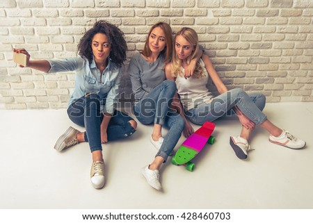 Beautiful young women of different nationalities are smiling and posing, while making selfie using smartphone - stock photo