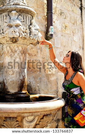 Beautiful young women pointing to fountain - stock photo