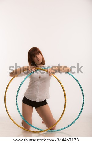 Beautiful young women posing with two hula hoops in white studio background - stock photo