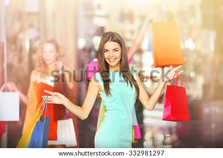 Beautiful young women with bags in shopping center - stock photo