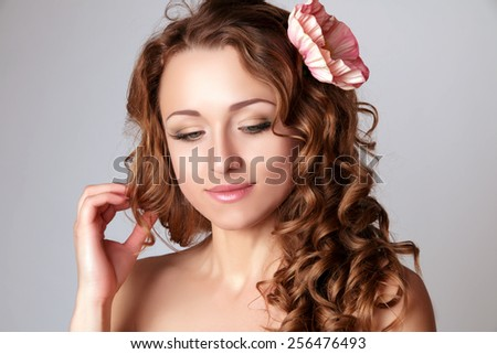 Beautiful Young Women with Curly and Flower. Touch Her Hair and Looking Down. Perfect Skin. Natural Make-up. - stock photo