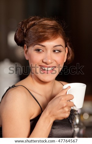 Beautiful young women with great smile and hairstyle sitting at a bar, drinking coffee. - stock photo