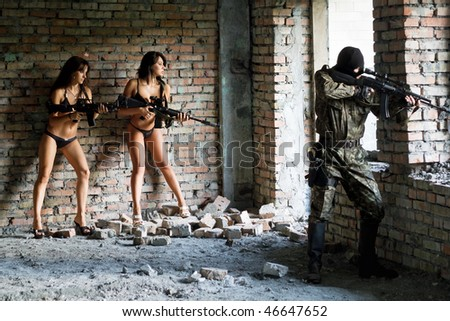 Beautiful young women with rifles and soldier - stock photo